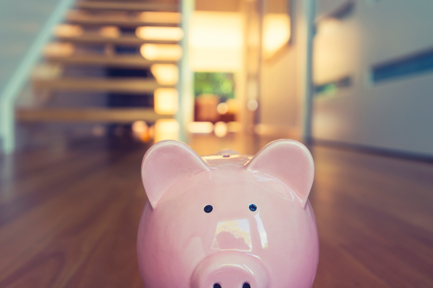 Piggy bank standing at front door with house interior in the background. Pig is pink in foreground and house is modern style.