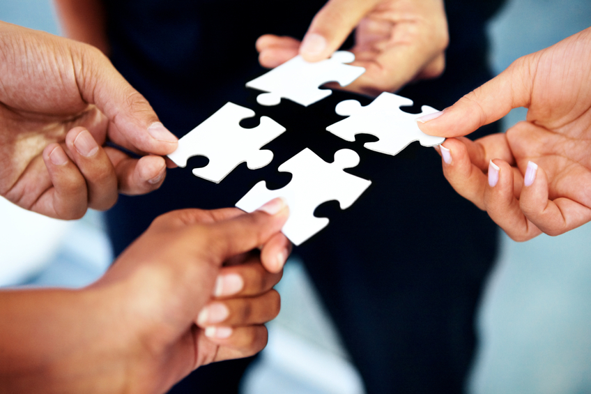 Closeup of a diverse group of people holding up pieces of a jigsaw puzzle