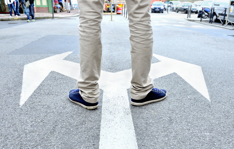 Arrows painted on asphalt. Young man standing hesitating to make a decision.