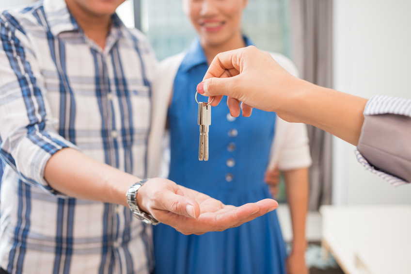 Hands of estate agent giving keys to the couple