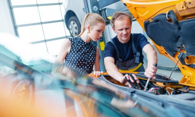 Auto mechanic with female customer looking under car hood.